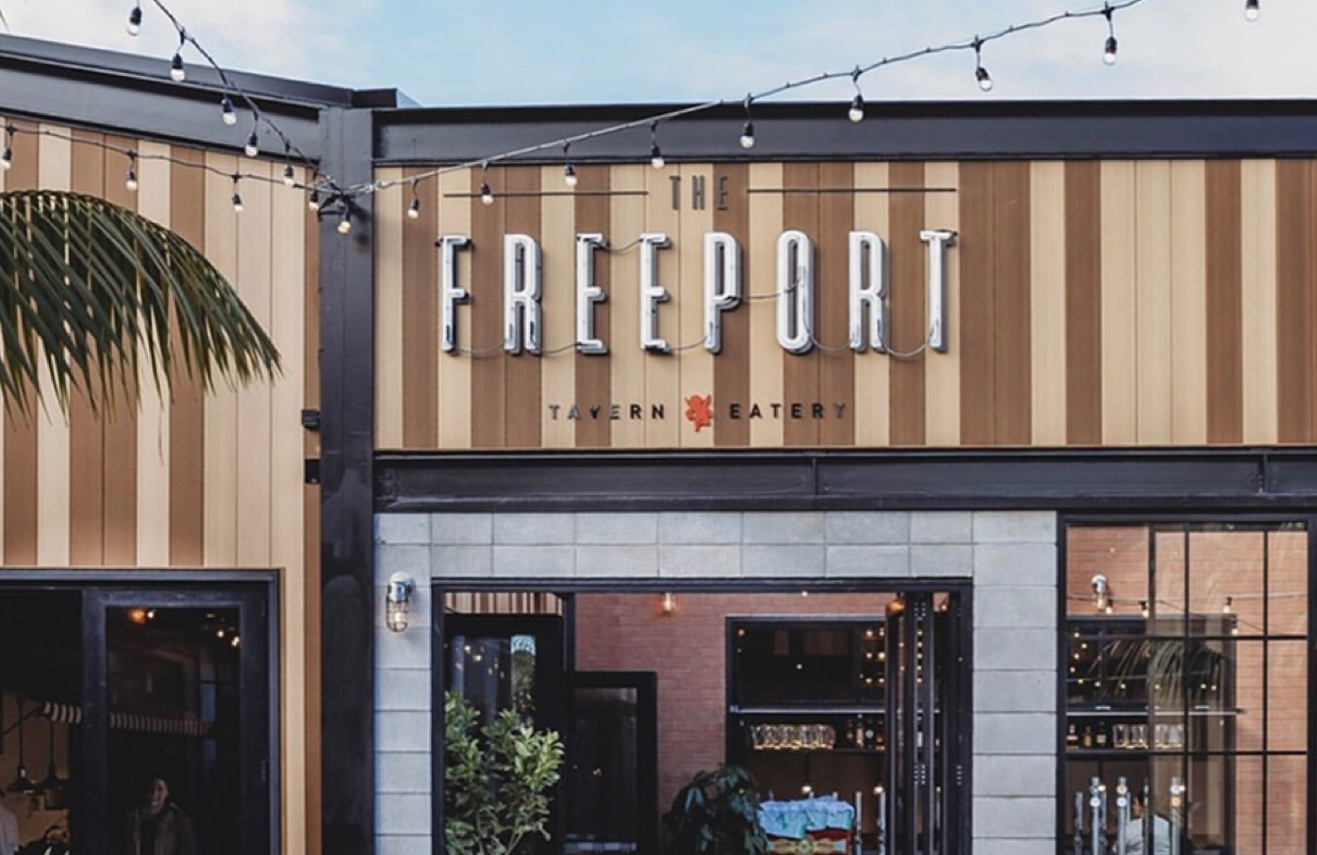The outside of a restaurant with the words Freeport Tavern eatery on the front