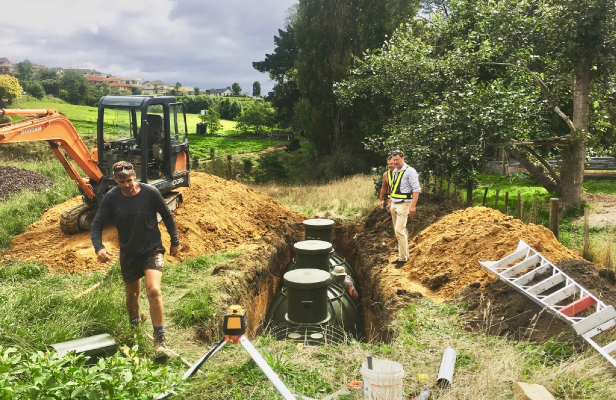 Men doing drainage work on a rural property that has a large septic tank buried in the ground