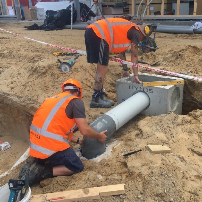 two men wearing high vis jackets work on a construction site, adjusting a huge pipe set into a concrete block