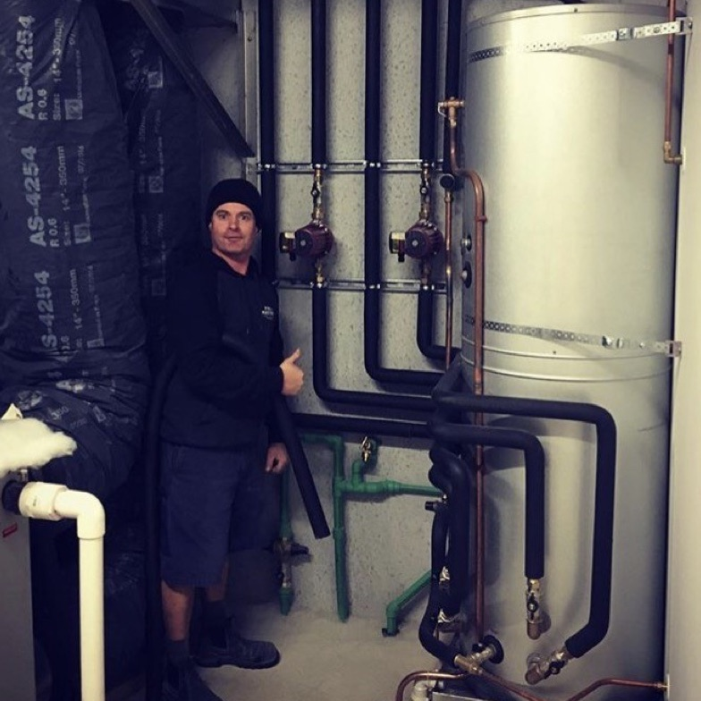 a man gives the thumbs up as he stands by a large cylinder, and a wall with lots of pipes on it