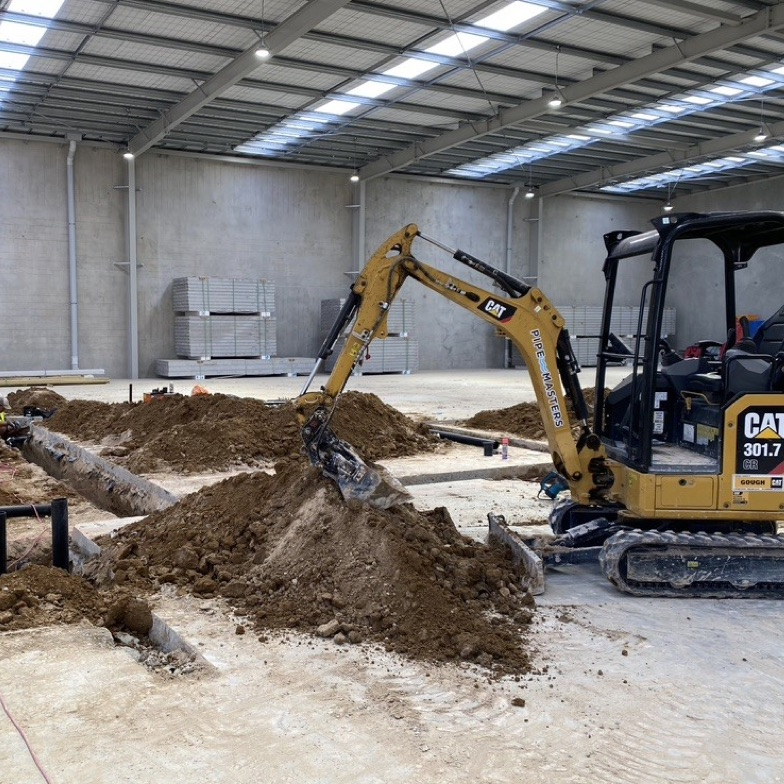 a digger moves soil in a large indoor setting with a high ceiling